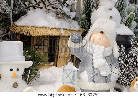 smiling face of adorable boy doll wearing white gray snow hat holding hurricane lamp lantern in the winter season background.