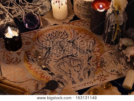 Close up of demon drawing on old parchment and magic ritual objects.  Halloween concept. Occult objects on table. There is no foreign text in the image, all symbols are imaginary and fantasy ones