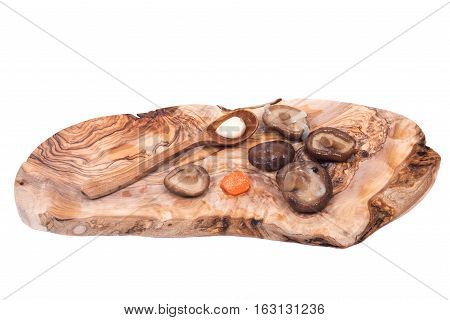 Shiitake marinated mushrooms with wooden spoon on olive wood cutting board isolated on white background