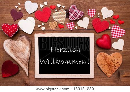 Chalkboard With German Text Herzlich Willkommen Means Welcome. Many Red Textile Hearts. Wooden Background With Vintage, Rustic Or Retro Style.