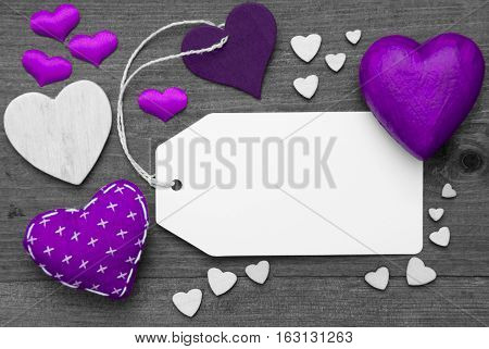 Label With Copy Space For Advertisement. Purple Textile Hearts On Wooden Gray Background. Retro Or Vintage Style. Black And White Image With Colored Hot Spot.