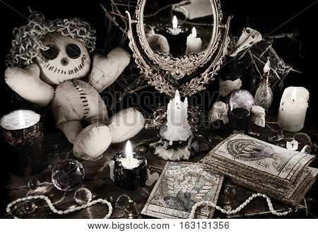 Magic ritual with voodoo doll, mirror, evil candles and tarot cards in vintage grunge style. Halloween concept, mystic or divination spell with occult and esoteric symbols