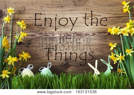 Wooden Background With English Quote Enjoy The Little Things. Easter Decoration Like Easter Eggs And Easter Bunny. Yellow Spring Flower Narcisssus With Gras. Card For Seasons Greetings
