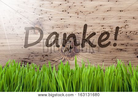 German Text Danke Means Thank You. Spring Season Greeting Card. Bright, Sunny And Aged Wooden Background With Gras.