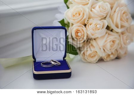 white gold wedding bands wedding rings from white gold in the blue box wedding jewelry wedding preparation a bouquet of white roses white light background