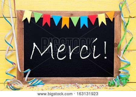 Blackboard With French Text Merci Means Thank You. Party Decoration Like Streamer And Confetti. Yellow Wooden Background. Greeting Card For Celebrations