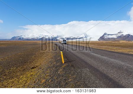 Car touring the ring road passes a tongue of the Vatna Glacier in South Iceland while clouds creep up over the snowcapped summit of the Hvannadalshnukur mountain