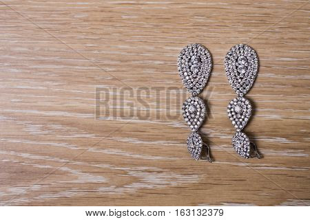 Bride earrings on a wooden background preparation for the wedding
