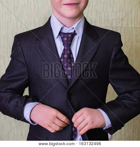 correct button on jacket hands close-up dressing man's style correcting sleeves boy preparing for the school