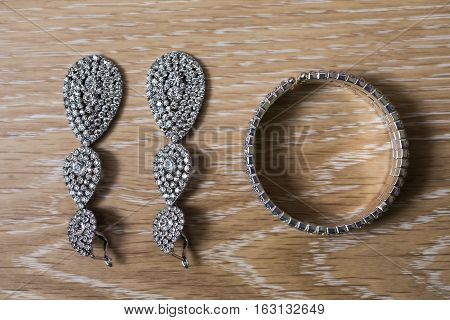 Bride earrings and bracelet on a wooden background preparation for the wedding
