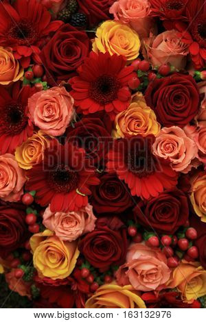 Mixed rose wedding arrangment in red pink orange and yellow
