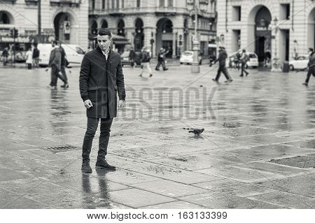 Full length of young man in coat walking under rain along square in European city. Turin center, Italy