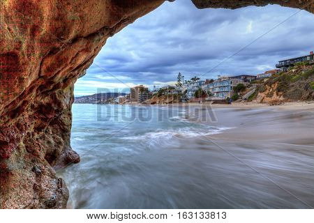 Sunset hits homes along Pearl Street Beach through a rock keyhole in Laguna Beach, California, USA