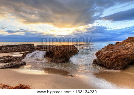 Sunset over the rocks at Pearl Street Beach in Laguna Beach, California, USA