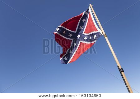 Confederate Flag on pole over blue sky.