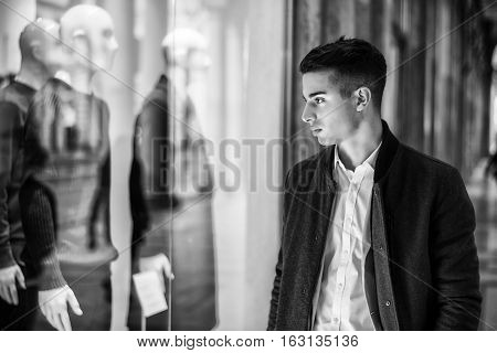 Handsome Young Man in Black Elegant Suit Looking at Displayed Fashion Items in Glass Window Boutique at the High Street Side.