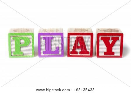 Alphabet blocks spelling the word Play isolated on white background.