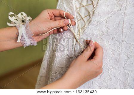 tighten wedding dress on bride, wedding day
