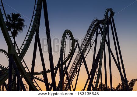 Roller Coaster Silhouette at Sunset with loops and dips