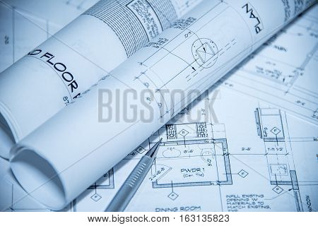 Architects workplace top view of blueprints. Architectural projects, blueprints, blueprint rolls on plans with pencil.