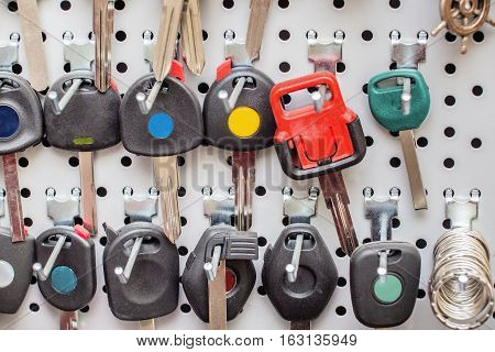 Various blank colorful car keys o a special wall in a workshop