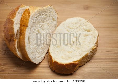 Three slices of French Bread on wooden cutting board.