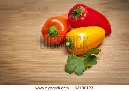 Three sweet peppers on wooden cutting board with a sprig of fresh cilantro.