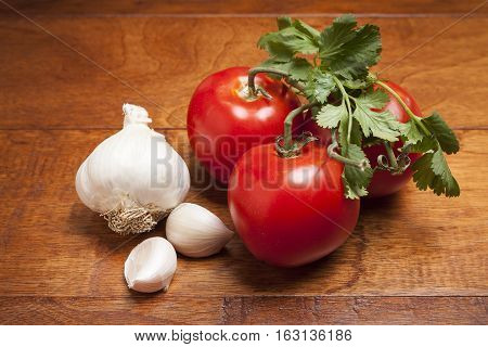 Ripe tomatoes with cloves of garlic on wooden background.