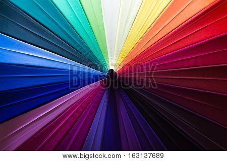 Background pattern of a variety of colored umbrellas.