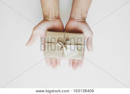 Hand holding brown gift box with paper note, on white background
