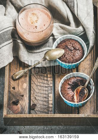 Chocolate souffle in individual blue baking cups and chocolate mocha coffee in glass in rustic wooden serving tray, copy space, selective focus