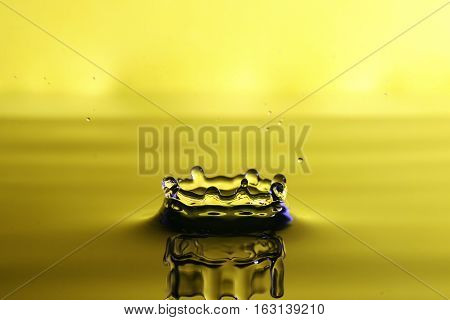Droplet of water from a splash yellow background