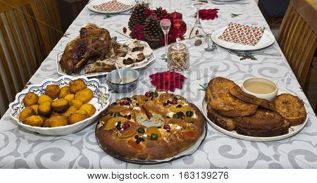 Table partly set for a traditional portuguese Christmas night dinner featuring roasted turkey and desserts such as pumpkin fritters cake and rabanadas a type of french toast