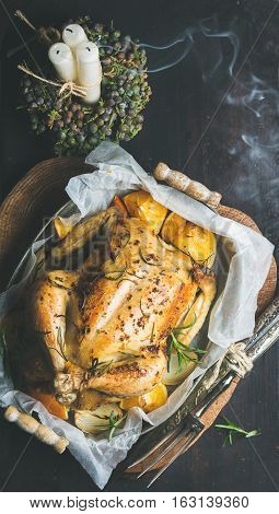Christmas holiday table set with roasted whole chicken stuffed with oranges, bulgur and rosemary, decorative candles with flying smoke over dark background. Top view, copy space, Slow food concept