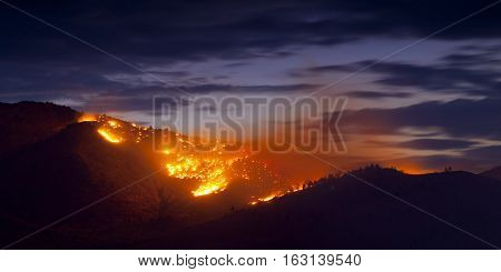 Burning Wildfire at Sunset in mountain range