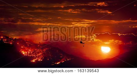 Burning Wildfire at Sunset with helicopter with water bucket fighting the fire