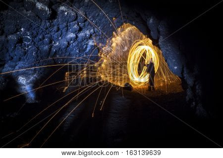 Fire spinning steel wool inside cave with showering sparks