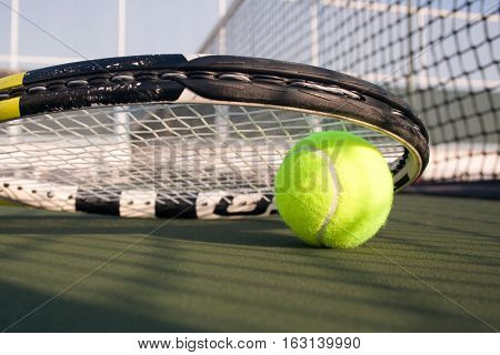 Tennis ball and a tennis racket on hard court