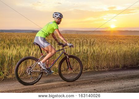 Biker woman riding rural road by mountain bike near the field against sunset with clouds.