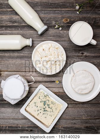 Dairy products on rustic wooden table. Sour cream milk cheese cottage cheese yogurt and bleu cheese. Top view.