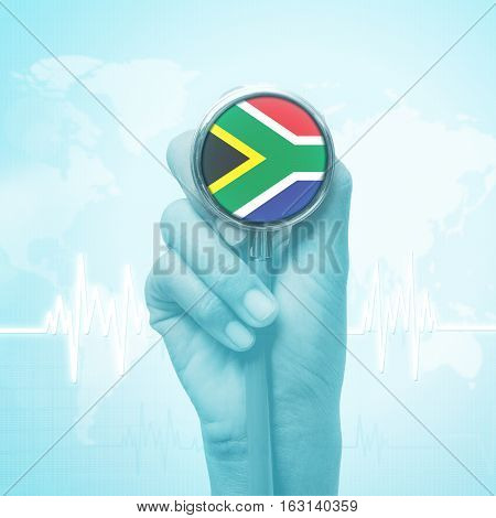 hand holding stethoscope with South Africa flag.