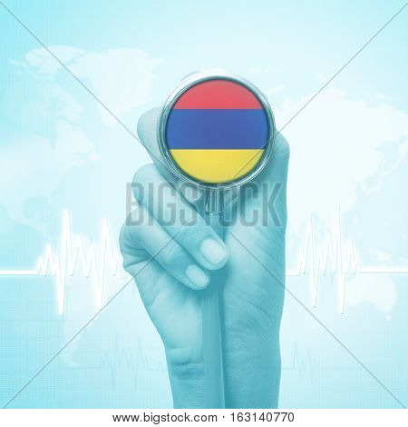 hand of doctor  holding stethoscope with Armenia flag.