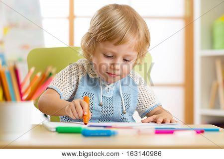Cute little kid is drawing with felt-tip pen in preschool