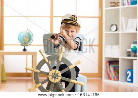 Child pretends to be a sailor. Little boy looking through spy glass playing at home.