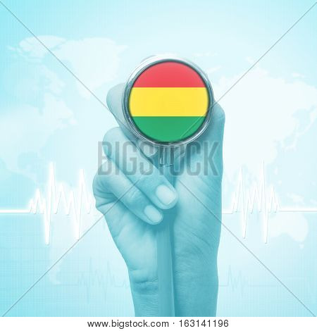 hand of doctor holding stethoscope with Bolivia flag.