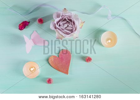 A Valentine day card with a rose flower, a paper butterfly, sweets, candles, a little cutout heart, and copyspace, slightly toned