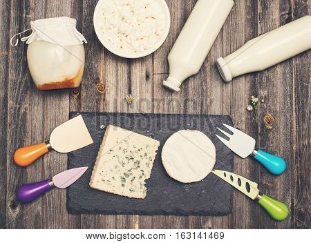 Retro styled vintage food background. Dairy products on rustic wooden table. Sour cream milk cheese cottage cheese yogurt and bleu cheese. Top view.