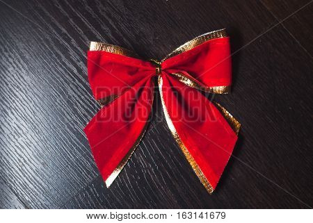 red bow on a black background, gold braid, decorations