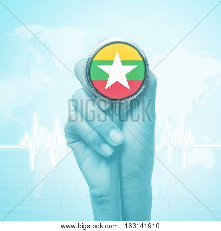 hand of doctor holding stethoscope with Burma flag.