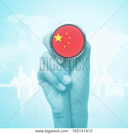 hand of doctor holding stethoscope with China flag.